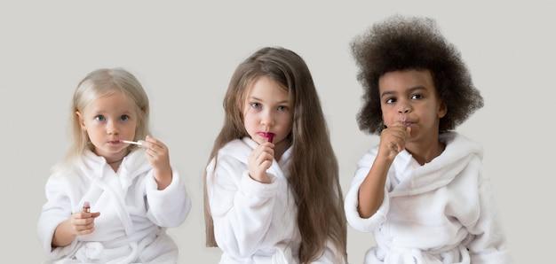 Namoradas de três meninas aplicam o batom.