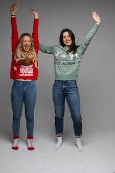 Namoradas despreocupadas em suéteres de inverno se divertindo.