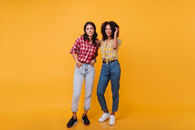 Namoradas elegantes em alto astral posando. foto completa de meninas em jeans da moda.