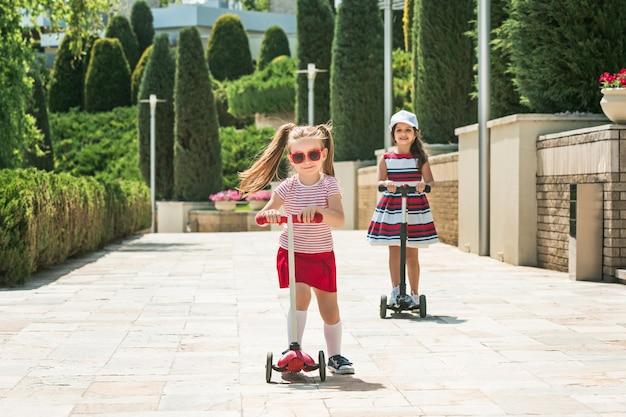 Namoradas em dia ensolarado. meninas em idade pré-escolar andando de scooter ao ar livre.
