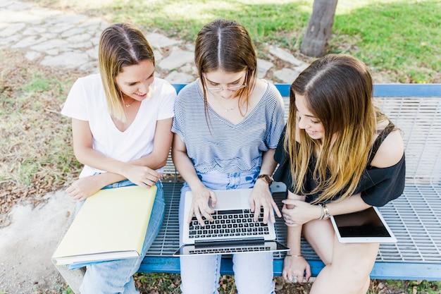 Namoradas, estudando com o laptop no banco