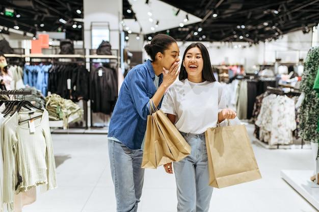 Namoradas felizes com compras em bolsas, loja de roupas. mulheres comprando em butique de moda, viciadas em compras, compradores com compras