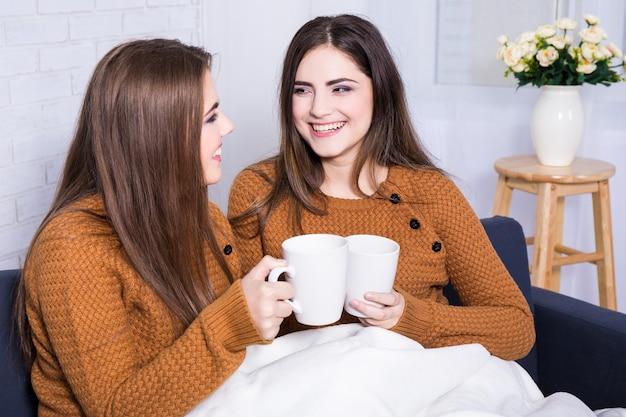 Namoradas felizes conversando e tomando café ou chá sentadas no sofá em casa