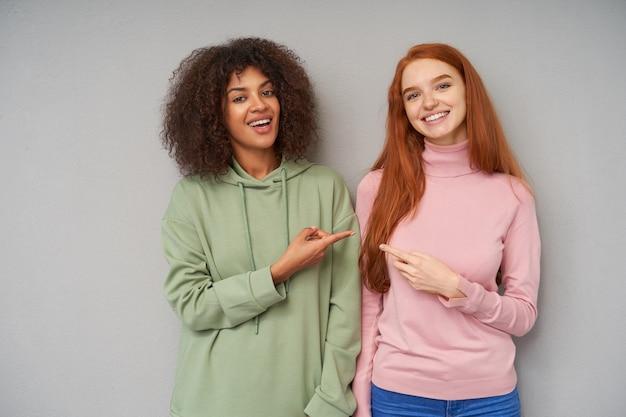 Namoradas jovens e atraentes alegres, vestidas com roupas casuais, mostrando-se com o dedo indicador e parecendo alegres com grandes sorrisos, isoladas sobre uma parede cinza