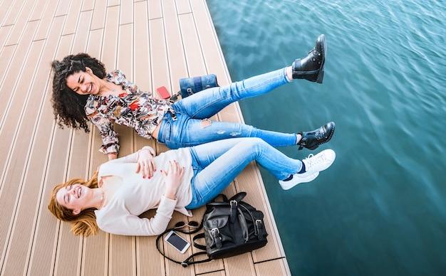 Namoradas multirraciais felizes se divertindo genuíno em docas do cais do molhe