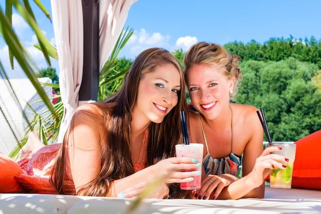 Namoradas na praia bar beber cocktails