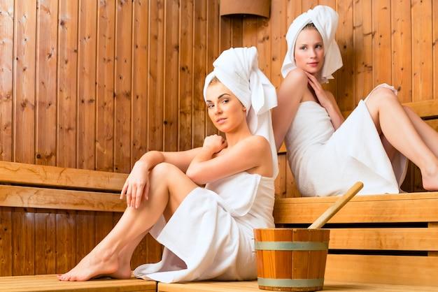 Namoradas no spa de bem-estar, desfrutando de infusão de sauna