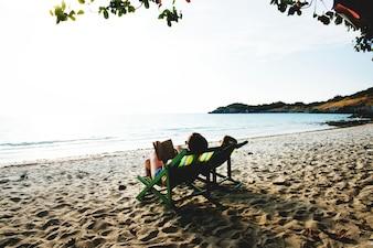 Namoradas relaxar e ler na praia