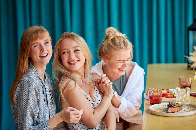 Namoradas riem, divirta-se sentado no restaurante