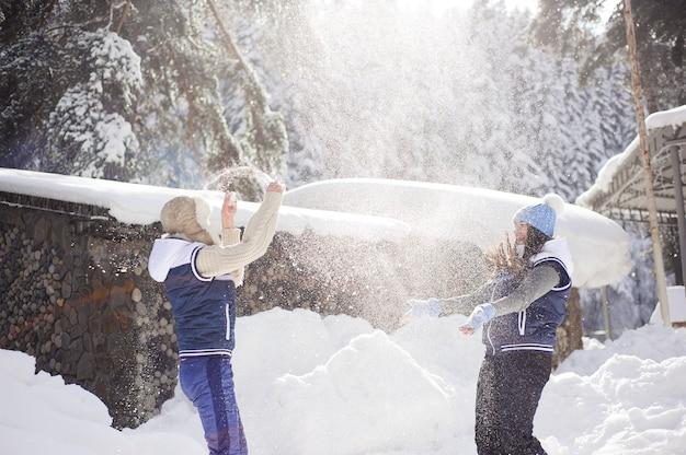 Namoradas se divertindo e curtindo a neve fresca em um lindo dia de inverno