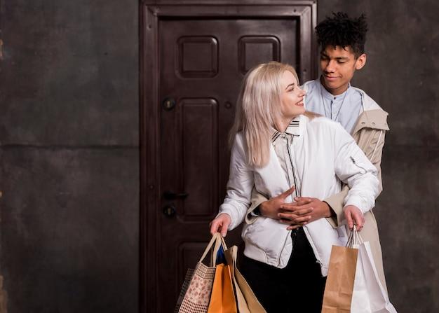 Namorado adolescente abraçando a namorada por trás segurando sacolas de compras nas mãos