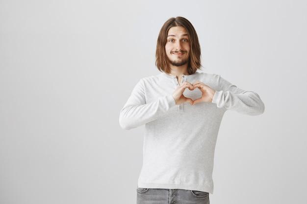 Namorado adorável mostrando um gesto de coração, expressando amor e carinho