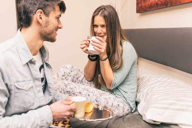 Namorado adorável trazer café da manhã para sua namorada de manhã