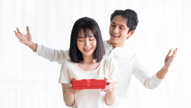 Namorado asiático dando presentes para a namorada no dia dos namorados