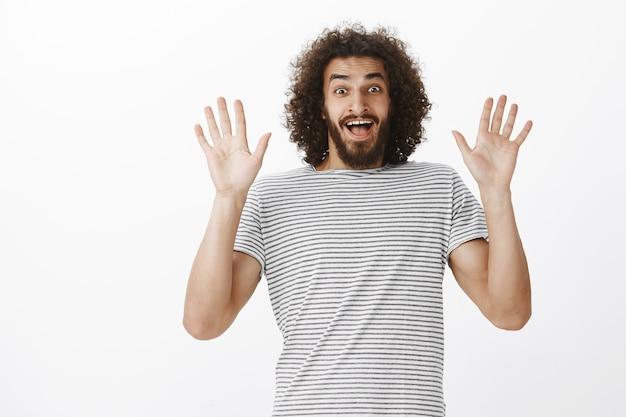 Namorado bonito maravilhado com cabelo e barba afro, levantando as palmas das mãos e sorrindo amplamente, ofegando de surpresa incrível