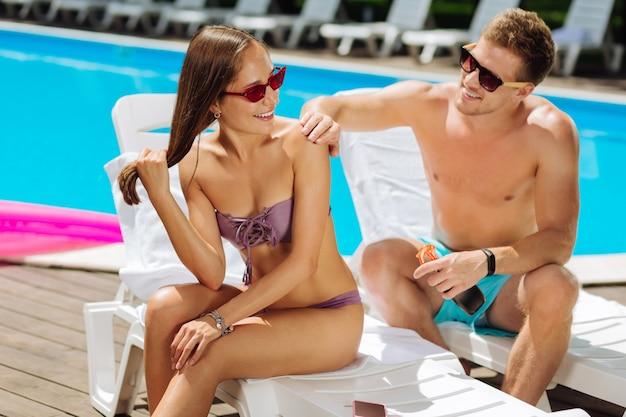 Namorado carinhoso usando óculos escuros e colocando creme de proteção solar na pele da namorada