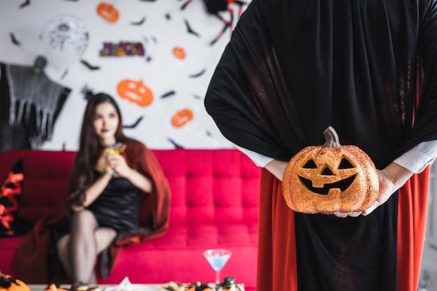 Namorado com a fantasia de drácula surpreendeu sua namorada segurando uma abóbora laranja de halloween atrás, com um fundo de namorada que estava antecipando o presente que ele recebeu de seu namorado.