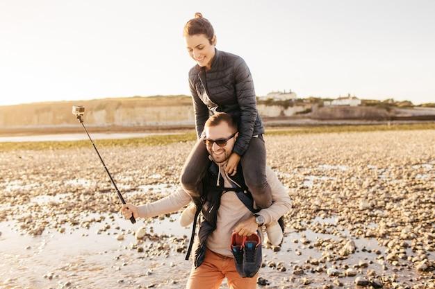 Namorado dá cavalinho para sua namorada, passear na costa, tirar fotos na câmera com bastão de selfie