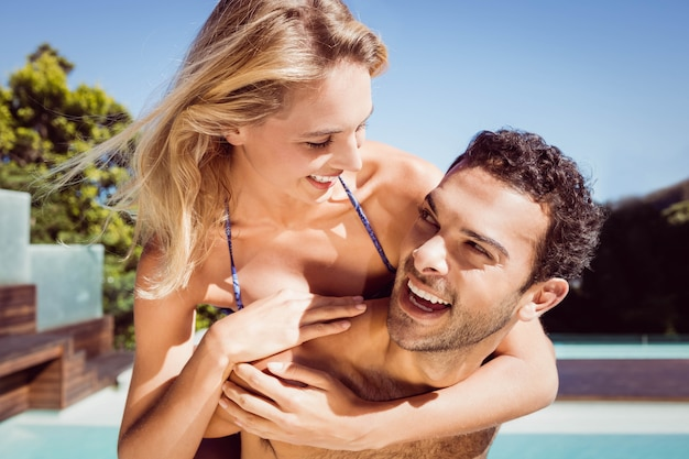 Namorado dando porquinho de volta para sua namorada à beira da piscina