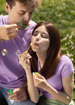 Namorado e namorada brincando com bolhas de sabão