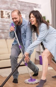 Namorado e namorada cantando e limpando a casa