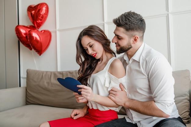 Namorado e namorada com cartão azul dos namorados e coração vermelho em forma de balões, sentado em casa no sofá
