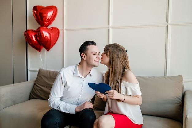 Namorado e namorada com coração azul em forma de cartão de dia dos namorados e balões vermelhos no sofá em casa