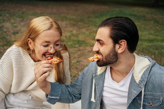 Namorado e namorada comendo pizza