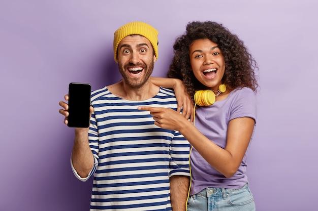 Namorado e namorada emocionalmente diversificados mostram um dispositivo de telefone inteligente moderno com tela de simulação para seu conteúdo promocional