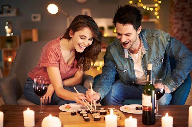 Namorado e namorada experimentando comida asiática
