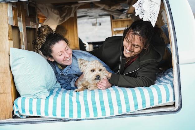 Namorado e namorada felizes se divertindo com um cachorro durante as férias de verão dentro de uma minivan vintage - foco principal na cara do cachorro