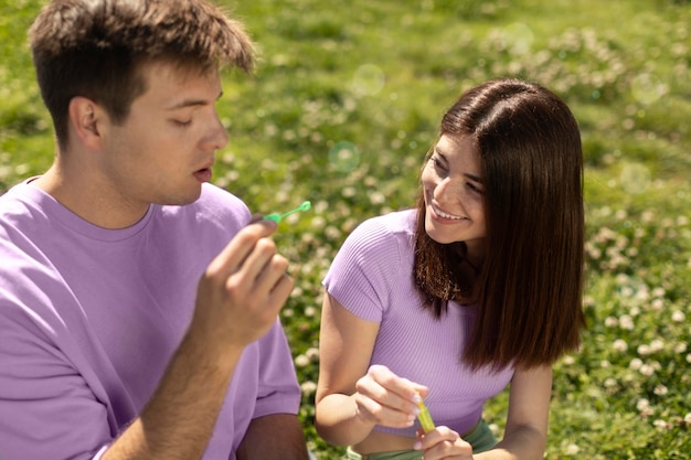 Namorado e namorada fofos brincando com bolhas de sabão