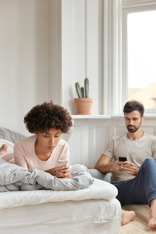 Namorado e namorada mestiços leem a notificação recebida, enviam sms enquanto descansam no quarto, ignoram a comunicação ao vivo, têm expressões sérias, focados no celular. vício e tecnologia