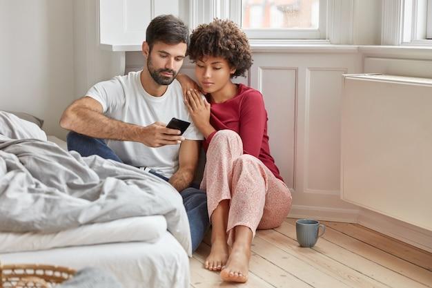 Namorado e namorada multiétnico relaxados sentados no chão em casa