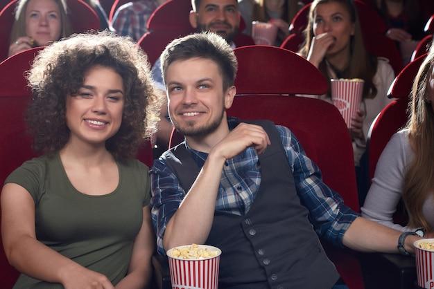 Namorado e namorada positivos e elegantes assistindo filme no cinema