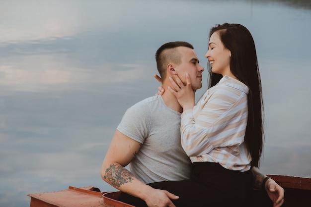 Namorado e namorada se abraçando no verão na praia à beira do rio
