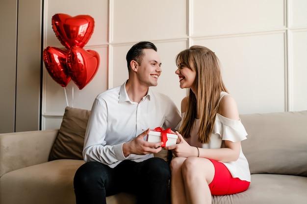Namorado e namorada trocam presentes românticos no sofá com balões em forma de coração em casa
