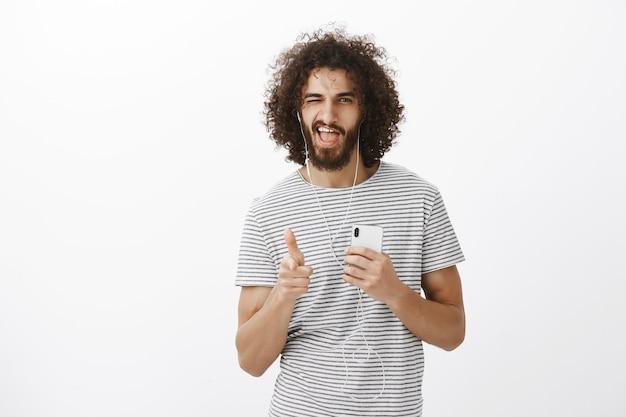 Namorado gostoso e confiante de cabelos cacheados em uma camiseta listrada, segurando um smartphone, apontando com uma arma de dedo na frente