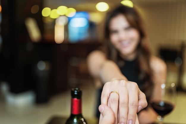 Namorado pedindo a mão da namorada com um anel de noivado em um restaurante