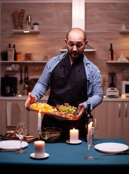 Namorado preparando um jantar romântico para a esposa na cozinha. homem preparando um jantar festivo com comida saudável, cozinhando um jantar romântico para sua mulher,