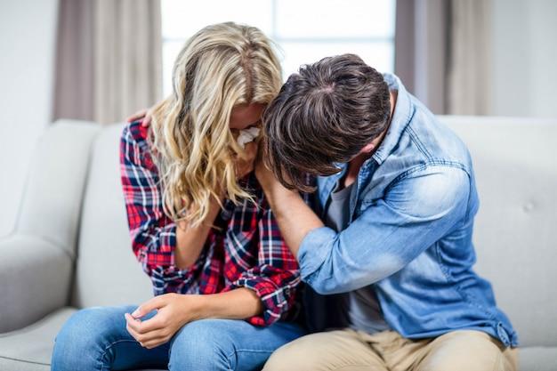 Namorado reconfortante namorada triste no sofá