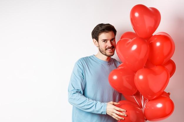 Namorado romântico traz balões de corações vermelhos no dia dos namorados, surpresa lon no encontro, em pé no branco