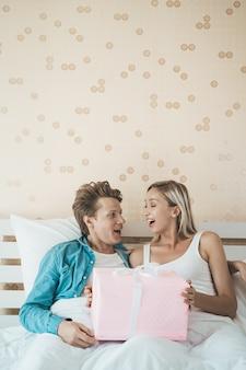 Namorado surpreender sua namorada com caixa de presente na cama