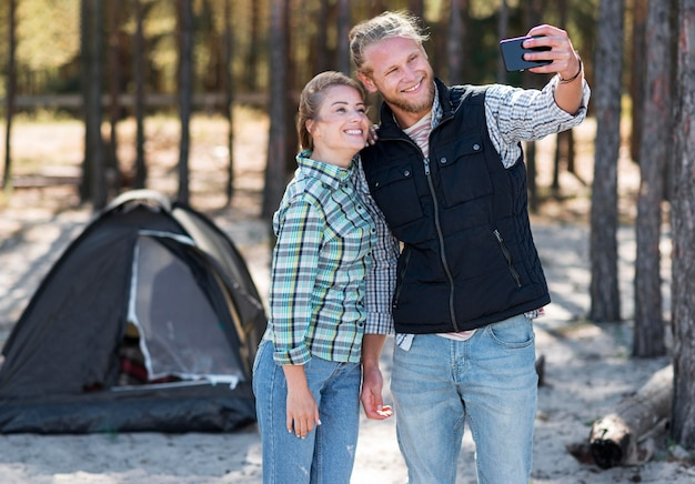 Namorado tirando uma selfie com sua barraca atrás