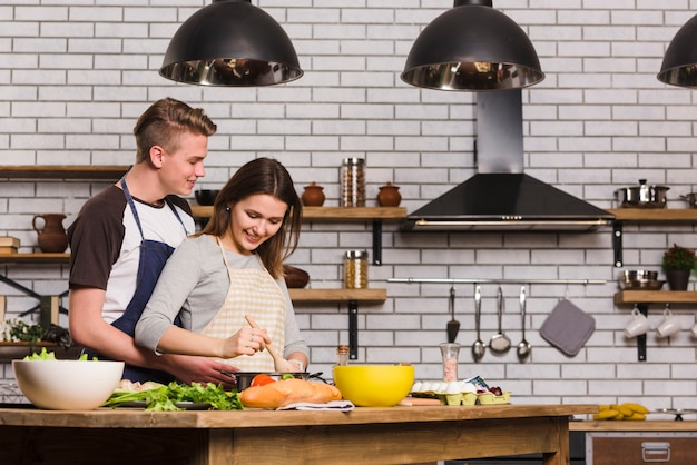 Namorados cozinhar na mesa na cozinha