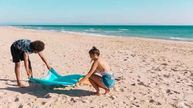 Namorados espalhando toalha na praia