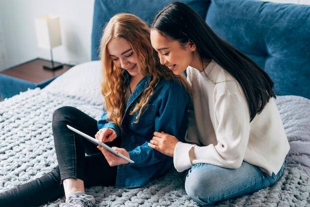 Namorados lésbicas alegres olhando para tablet