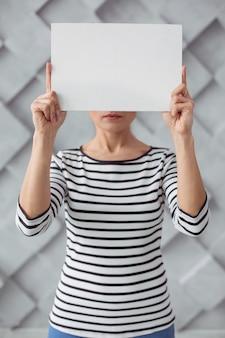 Não à violência. mulher jovem triste e deprimida em pé contra a parede, segurando uma folha de papel enquanto a mostra a você