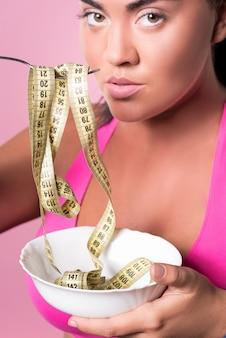 Não coma demais. perto de uma mulata bonita segurando o prato e o garfo na boca dela com fita métrica enrolada nele.