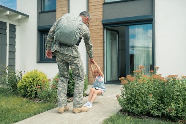 Não deixando ir. linda garota emocional se sentindo tocante enquanto não deixa ir o pai servindo nas forças armadas